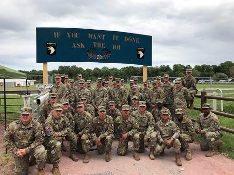 "Soldiers assigned to the 101st Airborne Division (Air Assault) pose for a photo before a sign bearing the division's motto ""If you want it done, ask the 101,"" June 2, 2019 in Carentan, Normandy, France."
