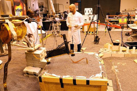 Engineers in a Mars-like test area at NASA's Jet Propulsion Laboratory try possible strategies to aid the Heat Flow and Physical Properties Package (HP3) on NASA's InSight lander, using engineering models of the lander, robotic arm and instrument. (NASA/JPL-Caltech)