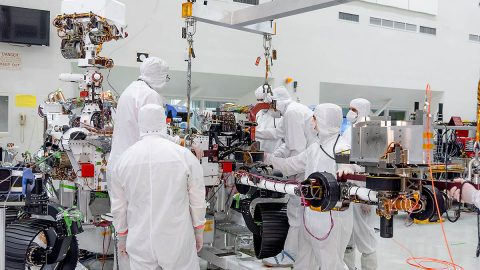 On June 21st, 2019, engineers at NASA's Jet Propulsion Laboratory install the main robotic arm on the Mars 2020 rover. Measuring 7 feet (2.1 meters) long, the arm will allow the rover to work as a human geologist would: by holding and using science tools with its turret. (NASA/JPL-Caltech)