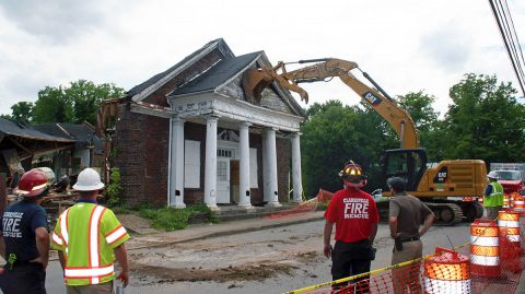 A Clarksville Street Department track hoe pushes down the damaged front of the old Wesley Chapel Christian Methodist Episcopal Church near downtown during a search Thursday.