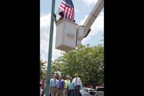 Roger Williams, a Clarksville Street Department technician, places a new American Flag at City Hall while Mayor Joe Pitts, Street Department staff Tommy Allbert, Tim Halbrooks and Brian Nelson, and Military Liaison Bill Harpel show pride in the effort to beautify the City with our country's most patriotic symbol.