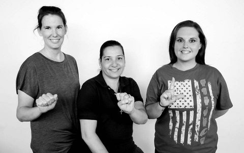 BACH employees, from left, Nicole Fitzwater, Wendyann Deasis-Dubois, and Kelly Money spell out A-S-L in American Sign Language. The trio facilitate a free American Sign Language chat at the hospital twice a month for beneficiaries and staff interested in ASL. All skill levels are welcome. The group meets at noon on the first Monday and third Wednesday of each month at the hospital. (U.S. Army photo by Fred Holly)
