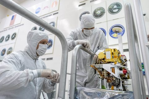 In this image taken June 25th, 2019, engineers install the SuperCam instrument on Mars 2020's rover. This image was taken in the Spacecraft Assembly Facility at NASA's Jet Propulsion Laboratory, Pasadena, California. (NASA/JPL-Caltech)