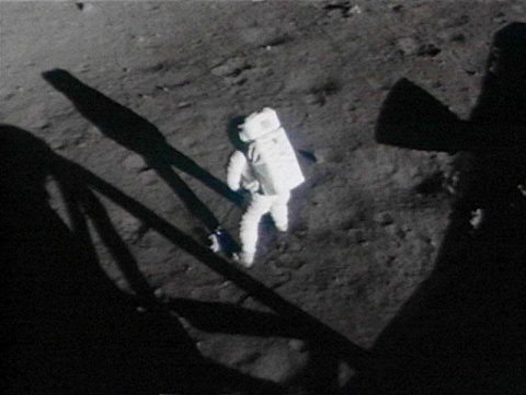 Still from the 16-mm film of Armstrong collecting the contingency sample. (NASA)