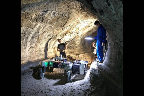 NASA's robotics team drives the test rover, CaveR, into Valentine Cave at Lava Beds National Monument. The science instruments, visible in the box-like structure pointing to one wall of the cave, will begin testing further downstream in the cave. One of the CaveR engineers is perched on a lava ledge, a marker of one of the lava flows in the cave. (NASA)