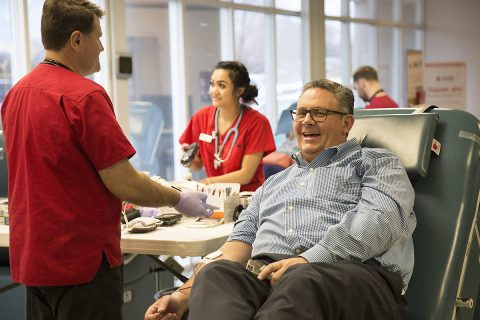 Thomas Brown finishes giving blood with American Red Cross staff member Alex White. (Amanda Romney, American Red Cross)