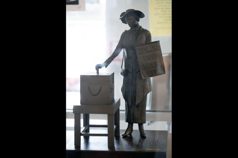 A woman casts her first vote in this miniature replica of the statue. (APSU)