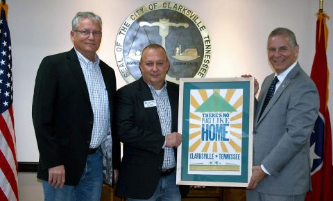"""Kevin Underwood, left, president of  Habitat for Humanity of Montgomery County, and Executive Director Rob Selkow present a Hatch Show Print celebrating Clarksville and """"home"""" to Clarksville Mayor Joe Pitts. The print is available for $20 at Habitat ReStore, 404 Madison Street."""
