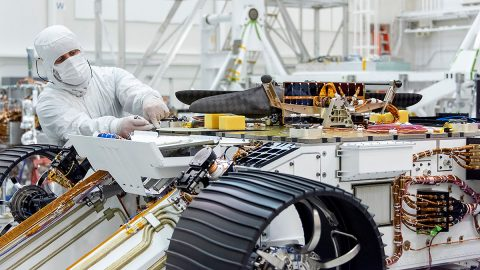 An engineer works on attaching NASA's Mars Helicopter to the belly of the Mars 2020 rover - which has been flipped over for that purpose - on Aug. 27, 2019, at the Jet Propulsion Laboratory in Pasadena, California. (NASA/JPL-Caltech)