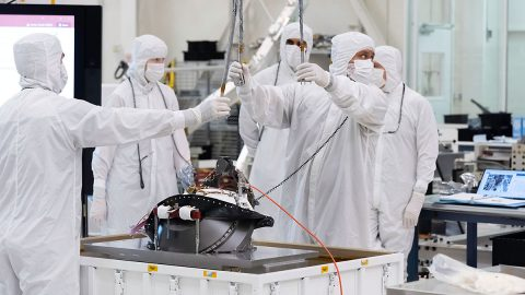 In this image, taken on Aug. 5, 2019, engineers at NASA's JPL lift the Mars 2020 rover's bit carousel from its storage container. The bit carousel is at the heart of the rover's Sample Caching System. (NASA/JPL-Caltech)