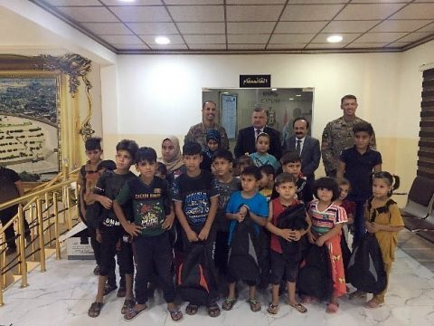 Lt. Col. Trevor Voekel and Command Sgt. Maj. Eddie Brewer of 1st Battalion, 327th Infantry Regiment pose for a photo with local children and the mayor of Mosul in Mosul, Iraq, Sept. 10, 2019. Task Force Ninewah donated 500 backpacks to the Mosul Mayor's office to distribute to children within the town. The U.S. Soldiers from the 101st Airborne Division are deployed from Fort Campbell, Kentucky. (Maj. Vonnie Wright, 1st Brigade Combat Team, 101st Airborne Division (AA) Public Affairs)