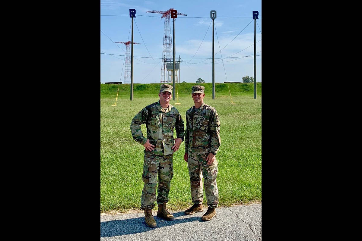 Austin Peay State University junior Alden Marvin, right, stands in front of the Army Airborne School towers. (APSU)
