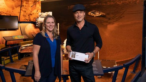 "The actor Brad Pitt (right) shows off his ""boarding pass"" for Mars with Jennifer Trosper (left), the Mars 2020 project systems engineer, at JPL on Sept. 6, 2019. You can send your name to Mars aboard NASA's Mars 2020 rover at https://go.nasa.gov/mars2020pass until Sept. 30, 2019. (NASA/JPL-Caltech)"