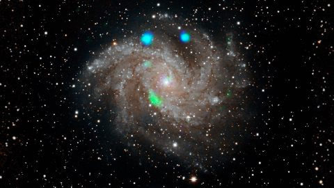 This visible-light image of the Fireworks galaxy (NGC 6946) comes from the Digital Sky Survey, and is overlaid with data from NASA's NuSTAR observatory (in blue and green). (NASA/JPL-Caltech)
