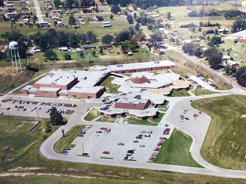 "A 1980's aerial view of Northwest High School (NWHS), in which a gym and classrooms as well as the ""400"" or ""vo-tech"" building had been added from the original structure. In 2014, a $17 million renovation was completed which added an auxiliary gym, a theatre, administrative wing, kitchen and indoor corridor to connect the 400 Building. (CMCSS Operations)"