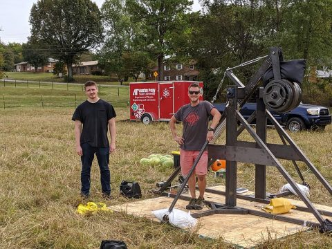 Austin Peay State University student Killian Prue (black shirt) and APSU physics lab manager Bryan Gaither (sunglasses) stand before Austin Peay's new trebuchet.