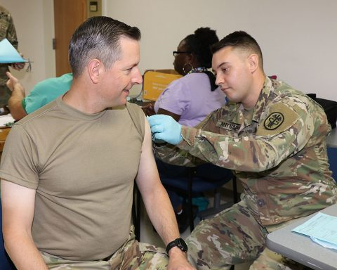 Pfc. Joshua Maynard, a combat medic specialist at Blanchfield Army Community Hospital, administers an influenza vaccination to Col. Patrick T. Birchfield, hospital commander, October 4th, during an employee influenza vaccination event. (U.S. Army photo by Maria Yager)