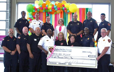 Clarksville Fire Rescue Chief Freddie Montgomery, front row center, joins with members of Fire Rescue to present a check for $8,000 to the YMCA's After Breast Cancer program at Thursday's Tickle Me Pink event at the Wilma Rudolph Event Center. Susan Harris and Angela Moody, both to Montgomery's right, lead CFR's annual T-shirt fundraiser which benefits ABC. Clarksville First Lady Cynthia Pitts, back row center, offered the invocation at Tickle Me Pink.