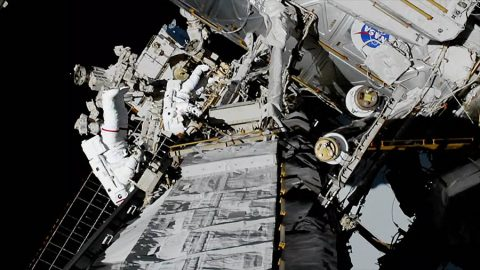 NASA spacewalkers Christina Koch (foreground, suit with red stripe) and Jessica Meir (suit with no stripes) replaced a failed battery charge-discharge unit with a new one during a 7-hour, 17-minute spacewalk. (NASA TV)
