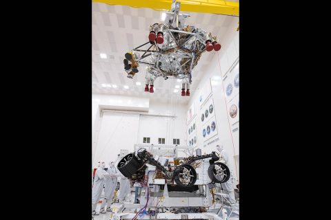 In this picture from September 2th8, 2019, engineers and technicians working on the Mars 2020 spacecraft at NASA's Jet Propulsion Laboratory in Pasadena, California, look on as a crane lifts the rocket-powered descent stage away from the rover after a test. (NASA/JPL-Caltech)