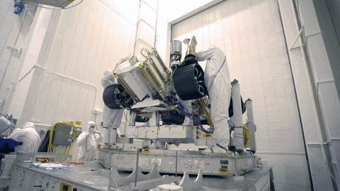 Bunny-suited engineers remove the inner layer of protective foil on NASA's Mars 2020 rover after it was moved to a different building at JPL for testing. (NASA)