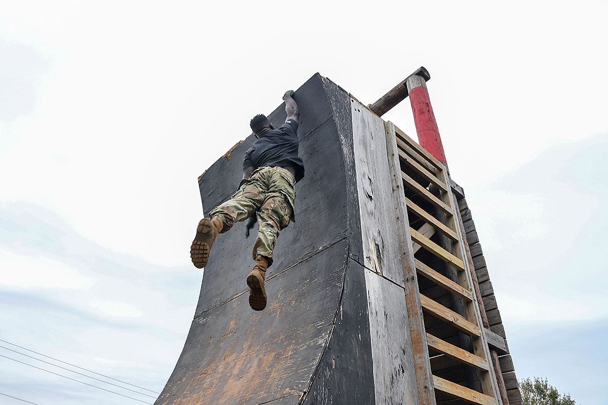 Capt. Chandler Smith, a member of the U.S. Army Warrior Fitness Team, hangs from a tower while conducting the 5th Special Forces Group obstacle course at Fort Campbell, Ky., Oct. 25 2019. Green Berets held multiple events throughout the day to show the physical fitness aspect of a special operations unit. (Sgt. Matthew Crane, 5th Special Forces Public Affairs Office)