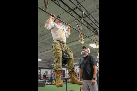 Professional CrossFit athlete Noah Olsen performs weighted pull-ups during an event at the 5th Special Forces gym, Fort Campbell, Ky., Oct. 25 2019. Green Berets held multiple events throughout the day to show the physical fitness aspect of a special operations unit. (Sgt. Matthew Crane, 5th Special Forces Public Affairs Office)