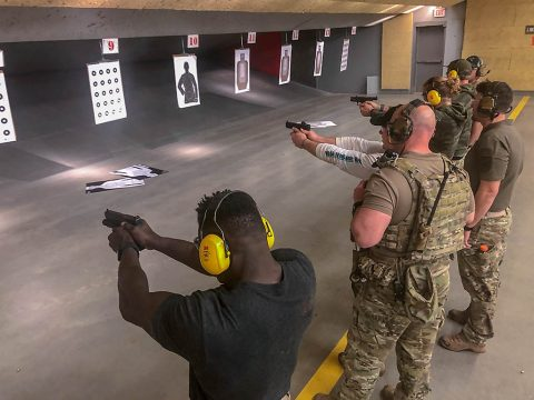 Capt. Chandler Smith, a member of the U.S. Army Warrior Fitness Team, along with professional CrossFit athlete Noah Ohlsen learn how to properly shoot handguns at the 5th Special Forces Group (Airborne) indoor shooting range, Fort Campbell, Ky., Oct. 25 2019. The Green Berets held multiple events throughout the day to show the different aspects of a special operations unit. (Sgt. Matthew Crane, 5th Special Forces Public Affairs Office)