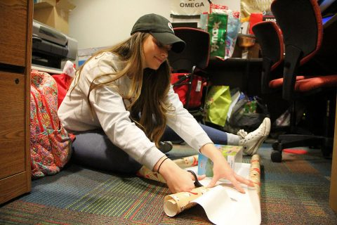 Anna Kail, former student employee in the office of Austin Peay State University Student Affairs, helps wrap gifts for the Help an Elf program in December 2018. (APSU)