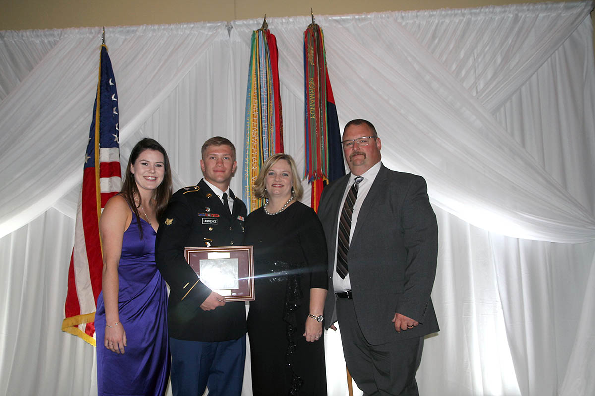 Spc. William Lawrence receives award at the Fort Campbell Chapter - Association of the United States Army Guardian's Gala by Maj. Gen. Brian E. Winski on Oct. 24 for his extraordinary actions taken as a combat medic during Operation Inherent Resolve. Spc. Lawrence stands with his parents at the conclusion of the event. From left Meghan Smith, U.S. Army Spc. William Lawrence, mother Linda Hicks, and stepfather Chris Hicks. (Maj. Vonnie Wright)