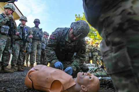 Sgt. Michael Hinkle, medic for 426th Brigade Support Battalion, 1st Brigade Combat Team, 101st Airborne Division (Air Assault), applies a chest seal to the training mannequin, Nov. 18, during a demonstration for Expert Field Medical Badge candidates at Fort Campbell. (Spc. Jeremy Lewis, 40th Public Affairs Detachment)
