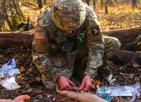 Second Lieutenant Shawn Ogden, a health services officer for 1st Battalion, 32nd Cavalry Regiment, 1st Brigade Combat Team, 101st Airborne Division (Air Assault), flushes an IV, Nov. 18, during a practice run for the Expert Field Medic Badge testing at Fort Campbell. The EFMB features rigorous tasks such as a 128-step patient evaluation. (Spc. Jeremy Lewis, 40th Public Affairs Detachment)
