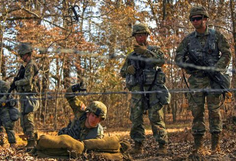 Spc. Morgan Shaffer, combat medic for Headquarters Support Company, Headquarters and Headquarters Battalion, 101st Airborne Division (Air Assault), throws a grappling hook to simulate checking for landmines, Nov. 20, during Expert Field Medic Badge combat training lane familiarization at Fort Campbell. (Spc. Jeremy Lewis, 40th Public Affairs Detachment)