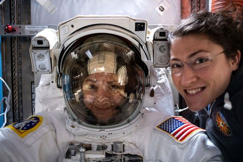 NASA astronaut Christina Koch (right) poses for a portrait with fellow Expedition 61 Flight Engineer Jessica Meir of NASA, who is inside a U.S. spacesuit for a fit check. The two are preparing for their first spacewalk together on Oct. 18, 2019, to replace a failed power controller on the International Space Station's P6 truss structure. (NASA)