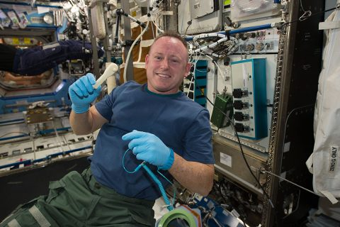 NASA Astronaut Barry (Butch) Wilmore holds a ratchet wrench created in 2014 with the 3D printer aboard the International Space Station using a design file transmitted from the ground. (NASA)