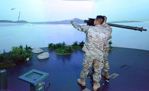 In the Stinger Dome, Staff Sgt. Ivan Peralta guides Sgt. 1st Class Arianna Cook as she aims a shoulder-fired Stinger missile at an enemy helicopter projected on the circular wall of the simulation center. A five-week class in the Man-Portable Air Defense System, or MANPADS, is being taught to infantry and armor Soldiers in a stop-gap effort to protect maneuver units from enemy aircraft, drones and cruise missiles. (Gary Sheftick)