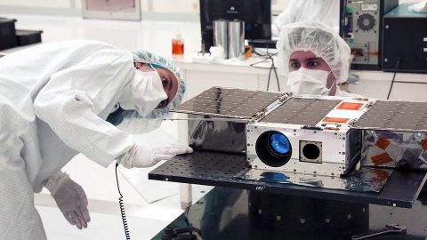 Left to right: Electrical Test Engineer Esha Murty and Integration and Test Lead Cody Colley prepare the ASTERIA spacecraft for mass-properties measurements in April 2017 prior to spacecraft delivery ahead of launch. ASTERIA was deployed from the International Space Station in November 2017. (NASA/JPL-Caltech)