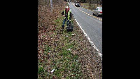 Litter Fighter: Clarksville Street Department worker Brennan Hudson picks up bottles, cans and trash along Dunbar Cave Road on Thursday.