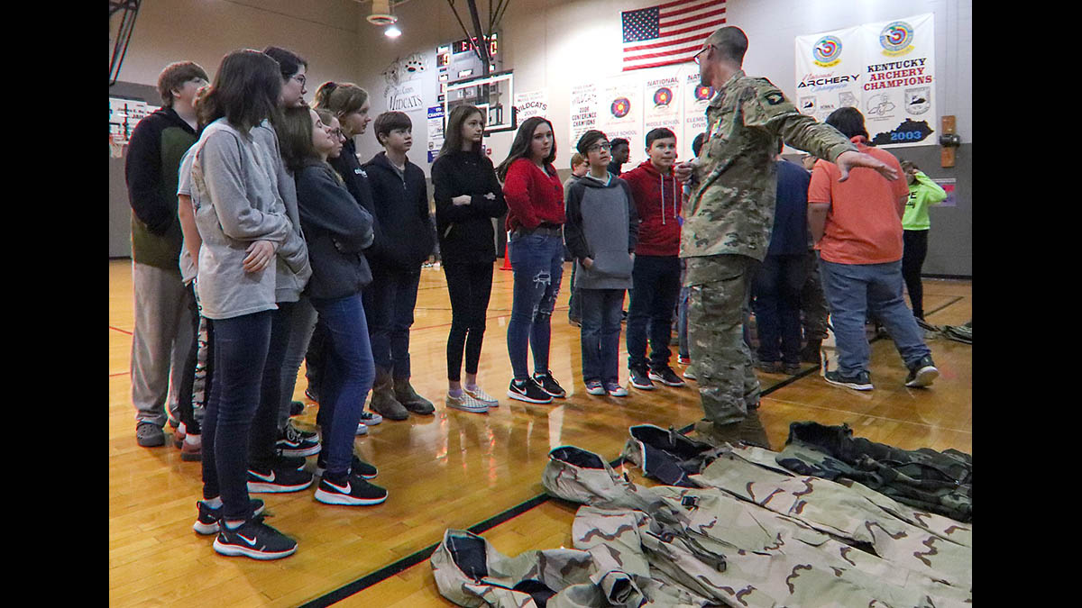 Pfc. Keneth Fouts, 74th Composite Truck Company, 129th Division Sustainment Support Battalion, 101st Airborne Division (Air Assault) Sustainment Brigade, shows students of Trigg County Middle School the different type of gear that 101st Airborne Division Soldiers wear such as wet weather gear, cold weather gear and operational camouflage pattern uniforms, Jan 28, in Cadiz, Ky. (Sgt. Aimee Nordin, 101st Airborne Division (AA) Sustainment Brigade Public Affairs)