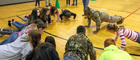 Spc. Walter Lacayo, 613th Movement Control Team, 129th Division Sustainment Support Battalion, 101st Airborne Division (Air Assault) Sustainment Brigade, leads the students of Trigg County Middle School through a warm-up exercise before their 10-meter water can challenge on Jan 28, in Cadiz, Ky. (Sgt. Aimee Nordin, 101st Airborne Division (AA) Sustainment Brigade Public Affairs)