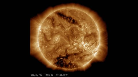 This image from NASA's Solar Dynamics Observatory on March 16, 2015, shows two dark spots, called coronal holes. The lower coronal hole, a polar coronal hole, was one of the biggest observed in decades. (NASA/SDO)