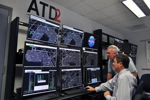 At NASA's air traffic management laboratory near the Dallas/Ft. Worth International Airport in Texas, researchers Al Capps (seated) and Paul Borchers demonstrate Airspace Technology Demonstration 2 tools that air traffic managers have been successfully testing since 2017 at the Charlotte Douglas International Airport in North Carolina to more efficiently direct departing traffic. (NASA / Jim Banke)