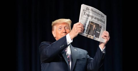 President Donald Trump holds up a copy of The Washington Post.