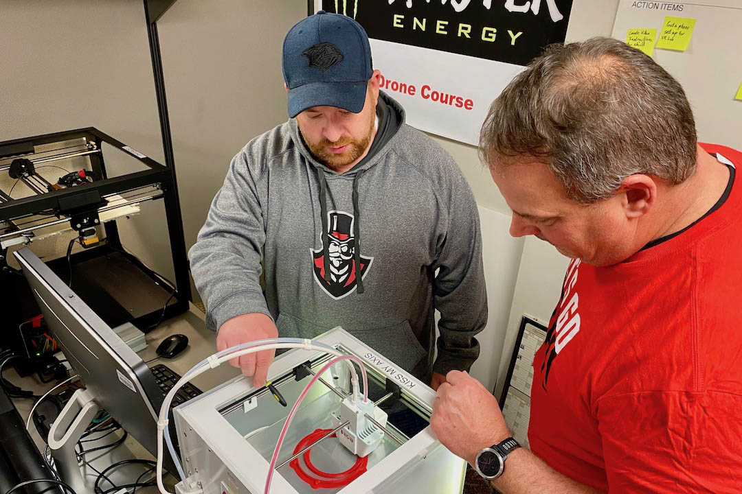 Ben Meisch and Austin Peay State University GIS Center Project Manager Doug Catellier examine a 3D printer at work on a shield frame. (APSU)