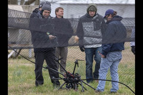 NASA researchers survey the crashed drone. A safety crash net was assembled to help save the vehicle from extensive damage. (NASA)
