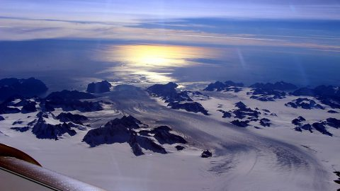 Greenland's Steenstrup Glacier, with the midmorning sun glinting off the Denmark Strait in the background. The image was taken during a NASA IceBridge airborne survey of the region in 2016. (NASA/Operation IceBridge)