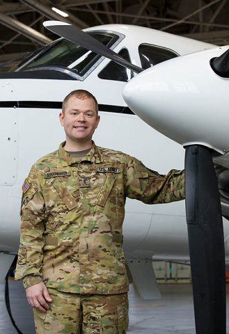 U.S. Army Reserve Chief Warrant Officer 3 Daniel Schoonmaker, a flight operations officer assigned to Company C, 2nd Battalion, 228th Aviation Regiment, 244th Expeditionary Combat Aviation Brigade, stands next to a C12-Huron plane used for executive transportation. (Sgt. Alexandra Shea)