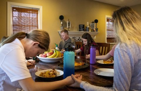 U.S. Army Reserve Chief Warrant Officer 3 Daniel Schoonmaker, assigned to 2nd Battalion, 228th Aviation Regiment, 244th Expeditionary Combat Aviation Brigade, prays with his family before enjoying dinner on March 11, 2020, at Carthage, North Carolina. The children are raised with Christian values and routinely eat meals, attend church and pray together. (Sgt. Alexandra Shea)