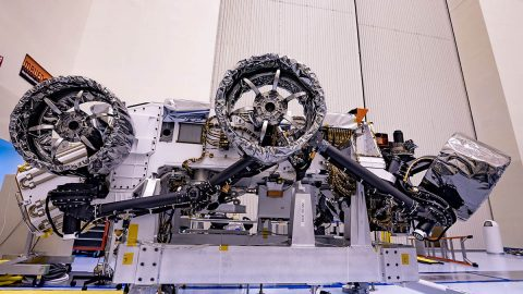 Three of the six flight wheels that will travel to Mars can be seen attached to NASA's Perseverance rover (which is inverted on a handling fixture) on March 30, 2020 at the Kennedy Space Center in Florida. The protective antistatic foil covering the wheels will be removed before launch this summer. (NASA/JPL-Caltech)