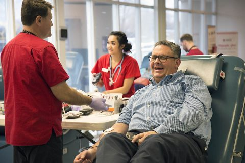 Thomas Brown finishes giving blood with American Red Cross staff member Alex White. (Amanda Romney/American Red Cross)